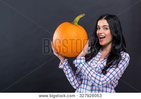 Happy Young Woman Holding A Pumpkin On A Black Background
