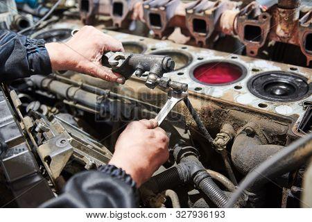 diesel truck engine repair service. Automobile mechanic tightening using wrench