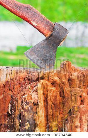 Old Hatchet In Wooden Log