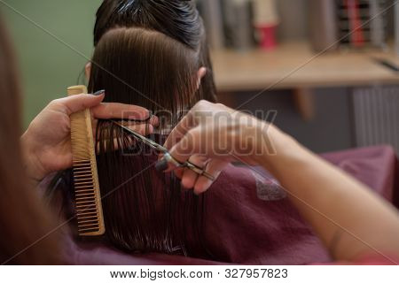 Stylist Hairdresser Makes A Hairstyle For A Cute Little Girl In A Beauty Salon.hairdressing, Hair Cu