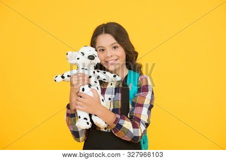 Preschool, play tool. Happy preschool girl on yellow background. Small child smile with toy. Early learning. Childcare. Daycare. Pre-school. Preschool education. Games and fun child went to preschool. poster