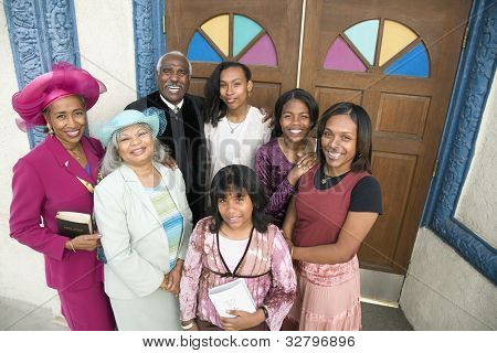 African American Reverend and parishioners in front of church