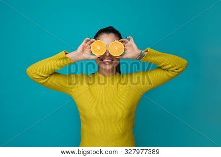 Front View Of Cheerful Brunette In Yellow Sweater Standing On Blue Isolated Background And Posing Wi