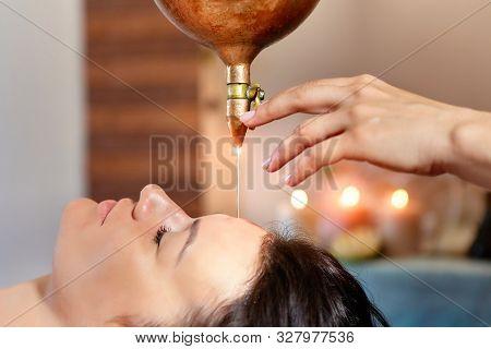 Ayurveda Massage Alternative Healing Therapy.beautiful Caucasian Female Getting Shirodhara Treatment