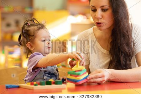 Teacher And Kid Girl Playing Colorful Block Toys In Creche