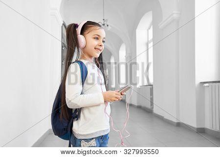 Pretty, Cheerful Schoolgirl In Break Between Lessons Listening Music With Headphones. Cute Child Sta