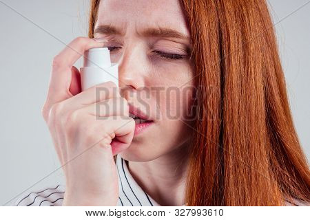 Redhead Businesswoman Tourist Student In A Striped Shirt Having Asthma Using The Asthma Inhaler For
