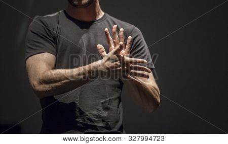 Sign Language Man Interpreter Gestures Over Stage During Public Event. Zenithal Spot Lighting His Ha