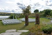 Place for wedding ceremony at the Lakeshore. Wedding arch decorated with flowers and white chairs on each side of archway outdoors poster
