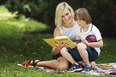 Affectionate mom reads a book to her special kid on a park lawn poster