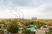 Thermal power station with residential buildings in the foreground. Smokestacks and cooling towers. Gray cloudy sky, yellowing edges of autumn trees. Air pollution concept. Environmental conservation poster