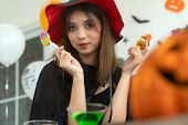 Beautiful young adult and teenager girl celebrating a Halloween party carnival Festival in Halloween costumes with food and drink on table. poster