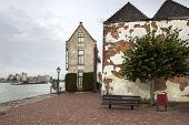 Historic buildings and a bench near river de Oude Maas in nostalgia Dordrecht in the Netherlands poster