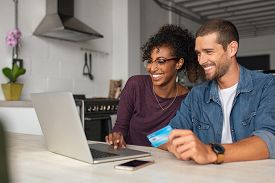Smiling young couple making shopping online with credit card and laptop at home. Happy multiethnic couple holding debit card while buying on ecommerce site using laptop.