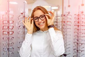 Happy Female Optometrist, Optician Is Standing With Many Glasses In Background In Optical Shop. Stan