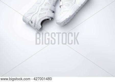 Top View Two White Kid Sneakers On The Side With Velcro Fasteners For Quick Shoeing With Copy Space