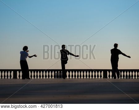 Silhouette Of Three Men Practicing Kung Fu On A Terrace By The Sea At Sunset.