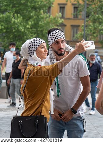 Parma, Italy - June 2021: Arab-looking Boy And Girl Who Are Using A Smartphone To Take A Picture Of