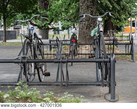 Three Old Bicycles Padlocked To The Rack.
