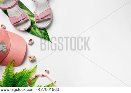 Top View With Summer Accessories. Girls Accessories, Pink Sandals And Cap With Green Tropical Leaves
