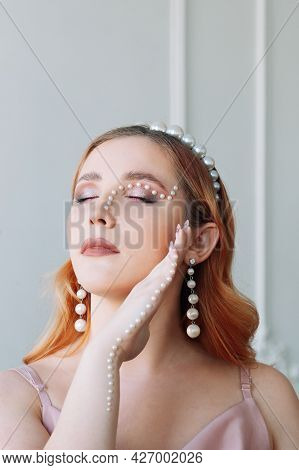Close-up Portrait Of A Red-haired And Pale-skinned Woman With Closed Eyes And Pearl Jewelry On Her H