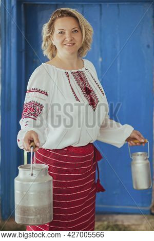Hostess In Embroidered Clothes With Milk Can. Retro Photo Of Ancient Ukrainian Life