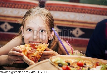 A Girl With Great Appetite And Pleasure Eats A Delicious Pizza At The Cafe. She Spends Her Free Time