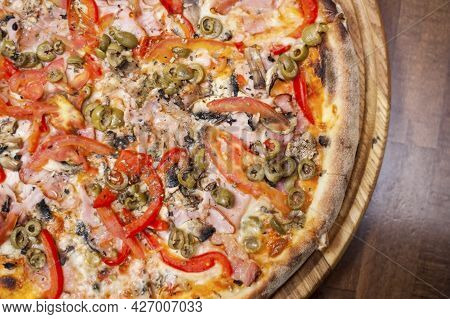 Delicious Pizza With Chicken Meat, Mushrooms, Tomatoes, Ham And Olives Is On A Special Wooden Pizza