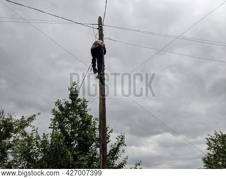Power Electrician Lineman At Work On Pole Against The Gloomy Sky.