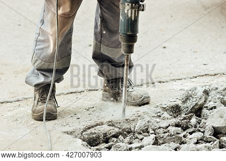 A Worker Repairs The Road Surface With A Jackhammer On A Summer Day. Construction Works On The Road.