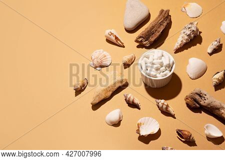 Calcium Or Collagen Capsules With Natural Materials, Seashells, Stone And Wood On Beige Background,