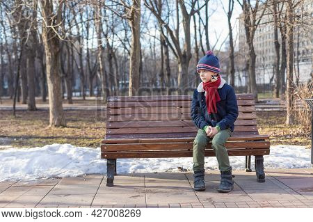 Caucasian Boy Sits In A Winter Park On A Bench Alone. The Boy Is Sad. Snow On The Ground In The Back
