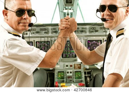 Two airline pilot wearing uniform with epaulettes and headset working in airliner during flight.
