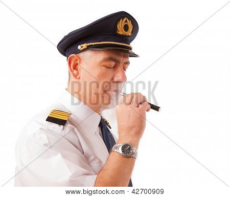 Airline pilot wearing uniform with epaulettes and hat smoking electronic cigarette, isolated on white.