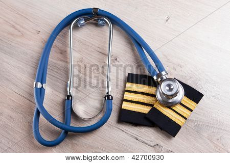 Close up of an airplane pilot epaluetes with doctor's stethoscope. Conceptual image of medical exam.