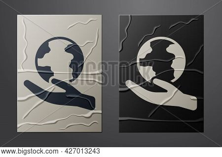 White Human Hand Holding Earth Globe Icon Isolated On Crumpled Paper Background. Save Earth Concept.