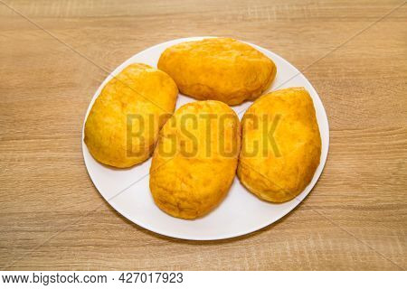Delicious Yellow Potato Pies On A White Round Plate On A Wooden Board Background. Bakery Products Na