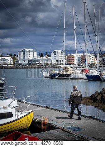 Fisherman Walking Down The Pier, Dressed In A Traditional Lopapeysa, Icelandic Wool Sweater.  Hafnaf