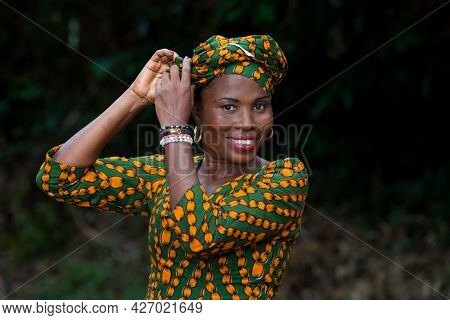Young African Woman Standing Up To Tie Loincloth On Her Head While Smiling At The Camera.