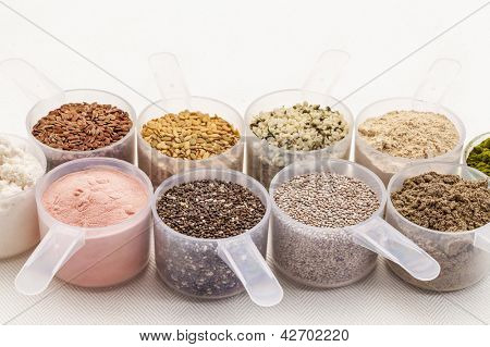 scoops of superfood - healthy seeds and powders (white and black chia, flax, hemp, pomegranate fruit powder, wheatgrass,whey protein, maca root) on white tablecloth