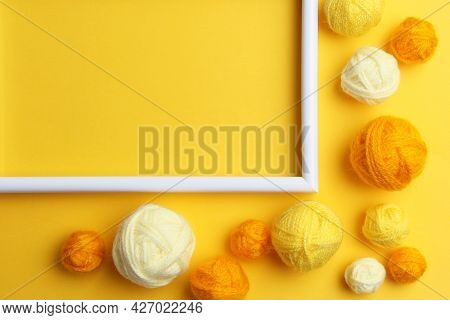A White Empty Frame And A Lot Of Yellow Balls Of Yarn Of Different Shades For Knitting Or Crocheting
