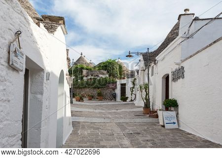 Alberobello, Puglia, Italy - June 26, 2019: Street In The Village Of Trulli With White Houses With C
