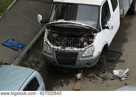Car Repair In The Yard. Truck With Open Bumper And Removed Wheel. Tools Are Scattered Around The Mac