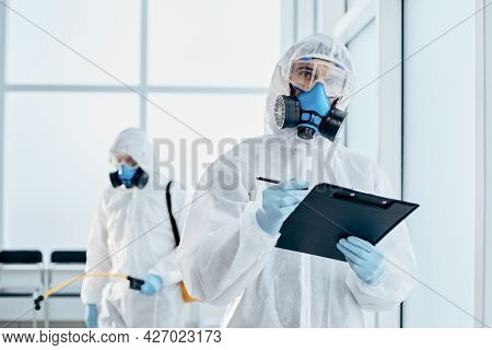 Professional Disinfector Taking Notes On The Clipboard.