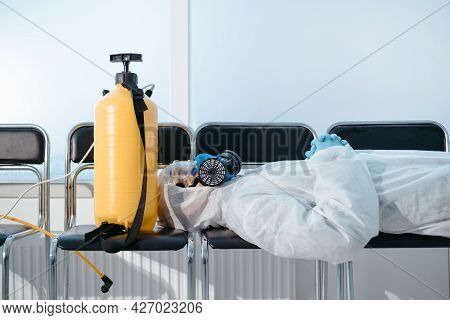 Very Tired Disinfector Is Sleeping On The Chairs In The Lobby Of The Hospital.