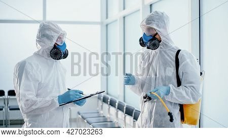 Team Of Professional Disinfector Making A Record Of The Work Done .