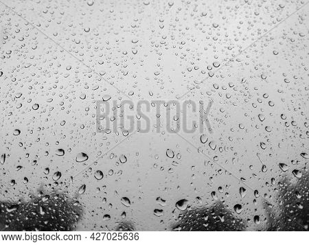 Raindrops On A Window In A Rainy Day, Blurry Grey Sky Background