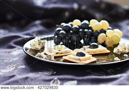 Three Blue Cheese Crackers With Grapes Are On A Black Plate.