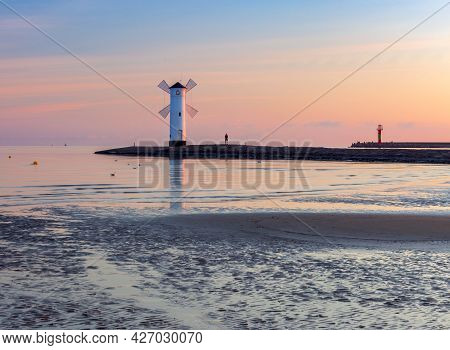 Swinoujscie. The Famous Mill Lighthouse At Sunrise.