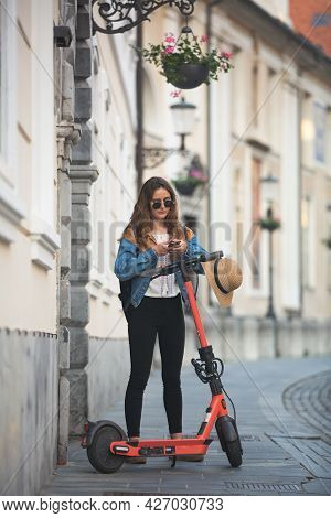 Electro-mobility. Traveler Unlocking An E-scooter Using An App On Her Smartphone. Traveler Exploring
